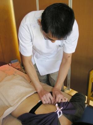 13 肩甲骨の間の反応のあるツボに鍼をします